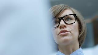 Low angle shot of beautiful business lady in eyeglasses talking to partners at work