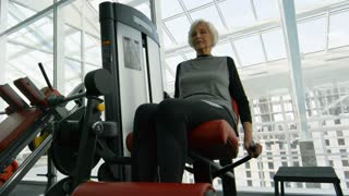 Low angle shot of determined senior woman in fitness clothes training on leg curl machine in gym