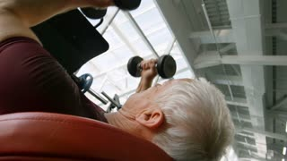 Low angle shot of elderly man with grey hair doing dumbbell bench press in gym