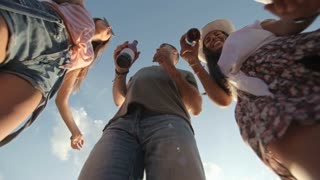 Low angle shot of happy group of friends holding beer bottles and dancing outdoors on summer day