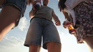 Low angle shot of happy group of friends with beer bottles waving hello to camera and dancing outdoors on summer day