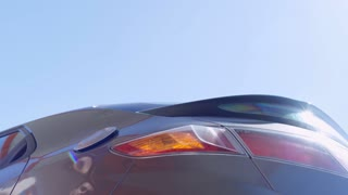 Low angle view of male hand inserting fuel nozzle into car tank at sunny day