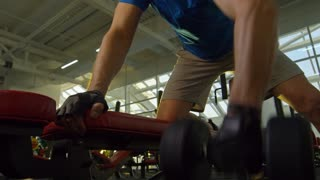 Low angle view of middle-aged man doing one-arm dumbbell rows at the gym