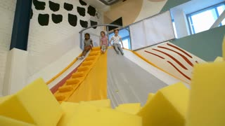 Low angle view of three little girls of different ethnicities sliding down into cube pit in indoor play center