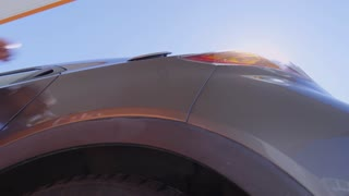 Low angle view of woman in blue coat opening fuel cap and inserting nozzle into car tank; sunlight shining at camera