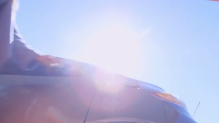 Low angle view of woman inserting fuel nozzle into car tank at gas station at sunny day