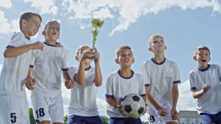 Low angle with slow motion of happy boys from junior soccer league holding gold cup and ball and jumping in celebration after winning championship