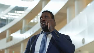 Low angled panning shot of african american businessman speaking on mobile phone in conference center