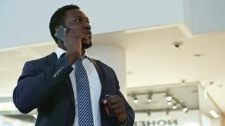 Low angled panning shot of cheerful african american businessman speaking on mobile phone in large modern office center