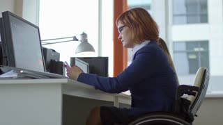 Low angled shot of paraplegic businesswoman on wheelchair sitting at office desk, smiling and speaking on mobile phone