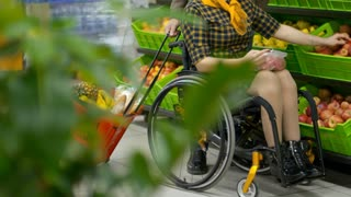 Low section of disabled woman on wheelchair taking apples from produce shelf in supermarket with help of her husband