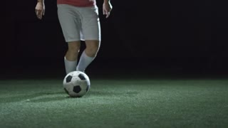 Low section of legs of female soccer athlete practicing dribbling a ball in dark sports arena with artificial turf on field