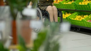 Low section of paraplegic woman riding wheelchair along produce shelves in supermarket while her husband walking behind and pulling cart with groceries