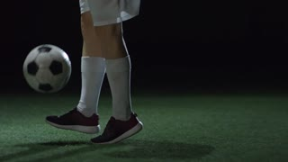 Low section of unrecognizable female athlete juggling soccer ball on artificial turf in dark indoor arena