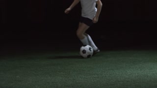 Low section of unrecognizable junior soccer player exercising with ball on artificial turf in dark indoor arena