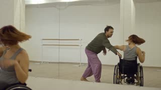 Male choreographer dancing with young paraplegic woman in wheelchair in studio during recovery therapy
