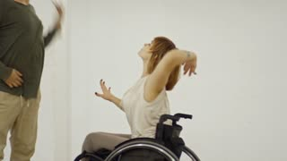 Male choreographer teaching disabled female partner how to dance in wheelchair