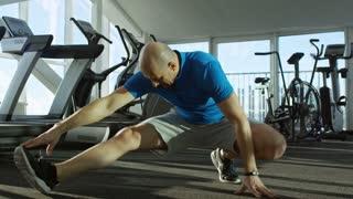 Mature man doing adductor stretching exercises at empty gym