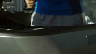 Mature man running on treadmill at the gym and drinking water from bottle, tilt up and down
