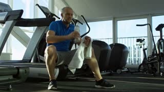Mature man sitting on treadmill during his break at the gym, drinking water from bottle and wiping his face with towel