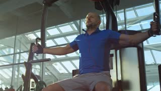 Mature man working out at the gym and doing butterfly with exercise machine