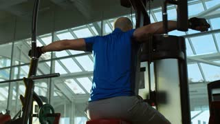 Mature man working out at the gym and doing reverse butterfly with exercise machine