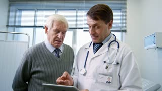 Medium shot mature male doctor in lab coat holding tablet and showing test results to happy senior man during appointment, then shaking his hand and congratulating