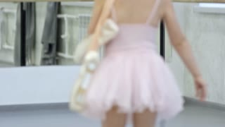 Medium shot of adorable little girl in pink leotard and tutu skirt carrying pointe shoes and running towards ballet barre in dance studio, then waving hand to greet her friends