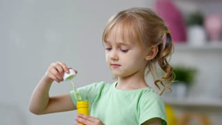 Medium shot of adorable little girl with wavy golden hair and two ponytails blowing soap bubbles with bubble blower toy