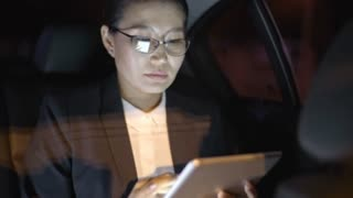 Medium shot of Asian businesswoman in glasses and suit sitting in backseat of moving car and working on tablet