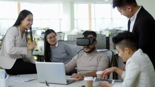 Medium shot of Asian office worker using virtual reality headset when sitting at desk surrounded by group of colleagues