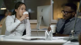 Medium shot of Asian woman and black man talking and drinking coffee when sitting at desk in office