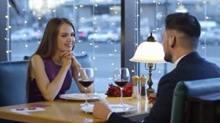 Medium shot of attractive young woman in purple dress sitting at table and listening to man in suit talking about himself while having dinner date in fancy restaurant