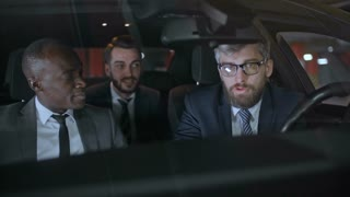 Medium shot of bearded businessman driving car in underground parking lot and chatting with African and Caucasian colleagues in suits