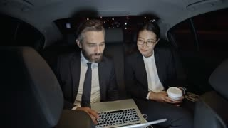 Medium shot of bearded businessman in suit and Asian businesswoman in glasses sitting in backseat of moving car and discussing work while looking at laptop