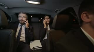 Medium shot of bearded businessman in suit and Asian businesswoman sitting in backseat of moving car and talking on mobile phones
