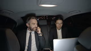 Medium shot of bearded businessman in suit talking on mobile phone and young Asian businesswoman in glasses working on laptop while riding in taxi at night