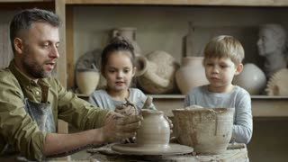 Medium shot of bearded father in apron talking and throwing rim of vase on spinning pottery wheel in workshop as cute elementary school-age children playing with clay