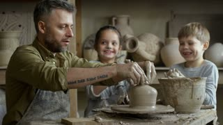 Medium shot of bearded male artisan in apron fixing rim of clay vase standing on pottery wheel as happy elementary school-age children playing with clay and laughing