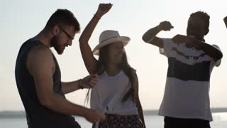Medium shot of bearded young man in glasses dancing with male and female friends on beach on hot summer day