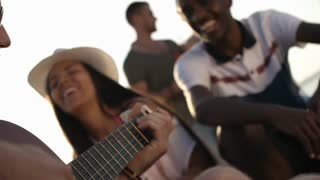 Medium shot of bearded young man playing guitar and singing outdoors as happy male and female friends laughing and clapping