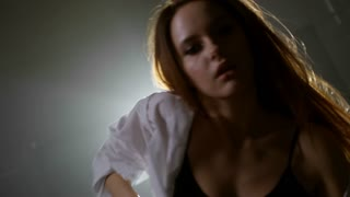 Medium shot of beautiful young woman in mens shirt moving seductively before camera in dark foggy studio with bright spotlight