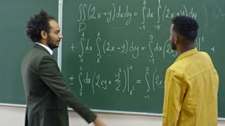 Medium shot of black male student standing at blackboard and looking at equations written on it when answering teacher's questions