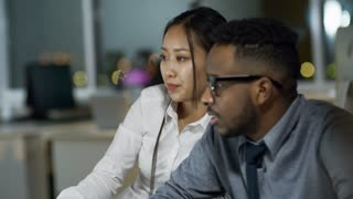 Medium shot of black man in glasses and Asian woman sitting at office desk and viewing something on computer when working late in the evening