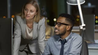 Medium shot of black man in glasses sitting at office desk and discussing work with Caucasian female colleague when using desktop computer late in the evening