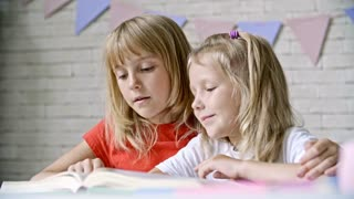 Medium shot of blond girl sitting before table and hugging her little sister while reading book together