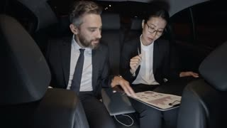 Medium shot of businessman in suit and Asian businesswoman in glasses riding in backseat of car and discussing charts and graphs on clipboard
