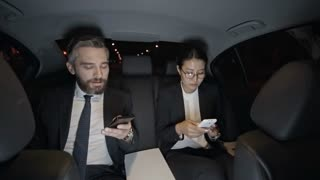 Medium shot of businessman in suit and Asian businesswoman in glasses sitting in backseat of moving car and looking at mobile phones