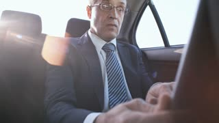 Medium shot of busy mature man in glasses and business suit using laptop computer and smartphone when going to work by taxi