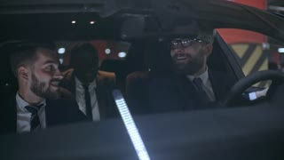 Medium shot of cheerful businessman wearing suit and glasses backing car into free space in underground parking lot and laughing with Caucasian and African male colleagues